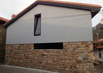 Fachada en gris con los aleros del color de las ventanas.