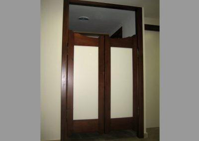 Puerta con jambas y bastidores en nogal y entrepaños en blanco roto.