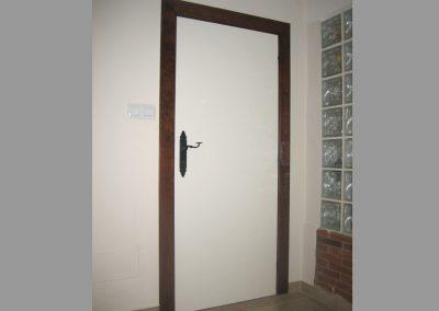 Puerta con jambas en nogal y hoja lacada en blanco roto.