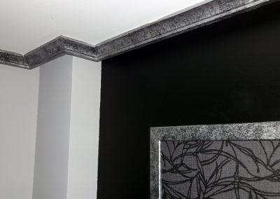 Cabecero en papel con jambas y molduras con efecto plata sobre negro.