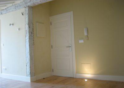 Salón con techos y carpintería en blanco roto y vigas maestras patinadas también en blanco roto.