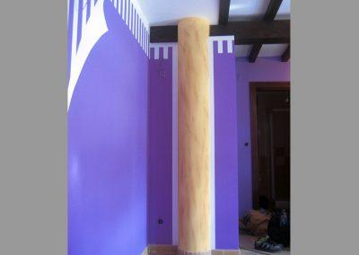 Pared con efecto de papel roto e imitación a piedra caliza en columna.