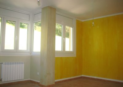 Salón con una zona en beige liso y otra con veladura rayada, separados por columna con rayas.