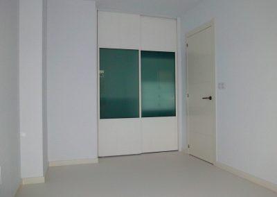 Dormitorio con suelo, puerta y armario lacado en blanco roto.
