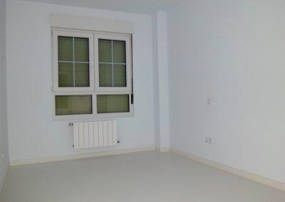 Dormitorio con suelo e interior de ventana de PVC lacado en blanco roto.