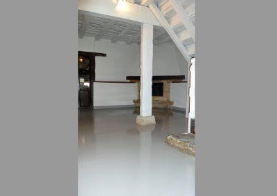 Salón con suelo lacado en gris.