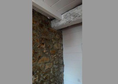 Pared de madera y techo lacado en blanco.