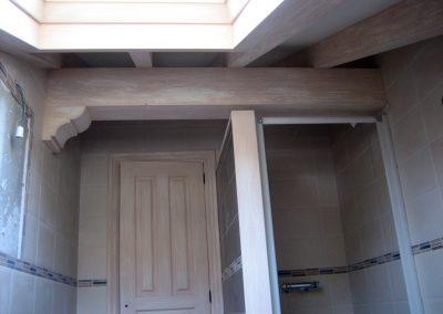 Baño con puerta y viguetas patinadas en marrón claro sobre fondo beige.