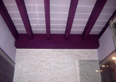 Baño con techo en blanco, vigas y viguetas en morado.