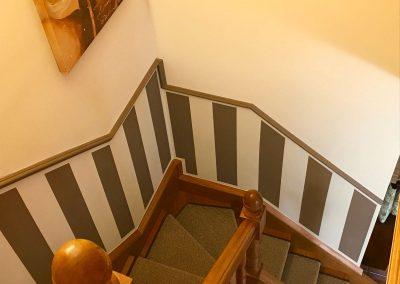 Zócalo de escalera con rayas y moldura.